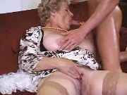 Old chesty witch in stockings spoils guy on sofa