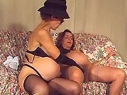 Two pregnant ladies in stockings relax on sofa