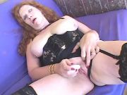 Redhead granny in stockings relaxes with sextoys
