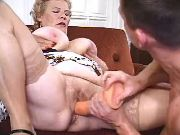 Nasty old dama licked and dildoed by guy on sofa