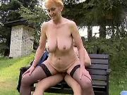 Hot busty granny in stockings rides cock in park