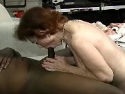 Depraved granny sucks huge chocolate cock on sofa